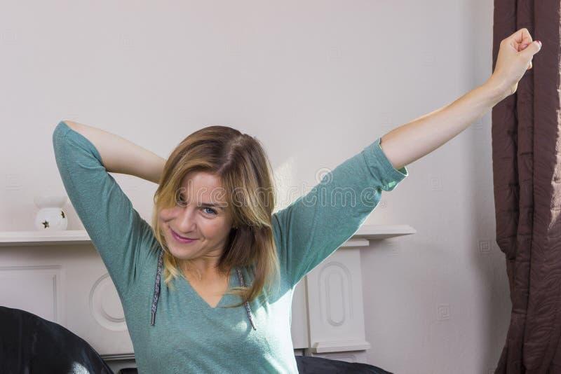 La fille stratching dans la chambre à coucher se réveillent photo libre de droits