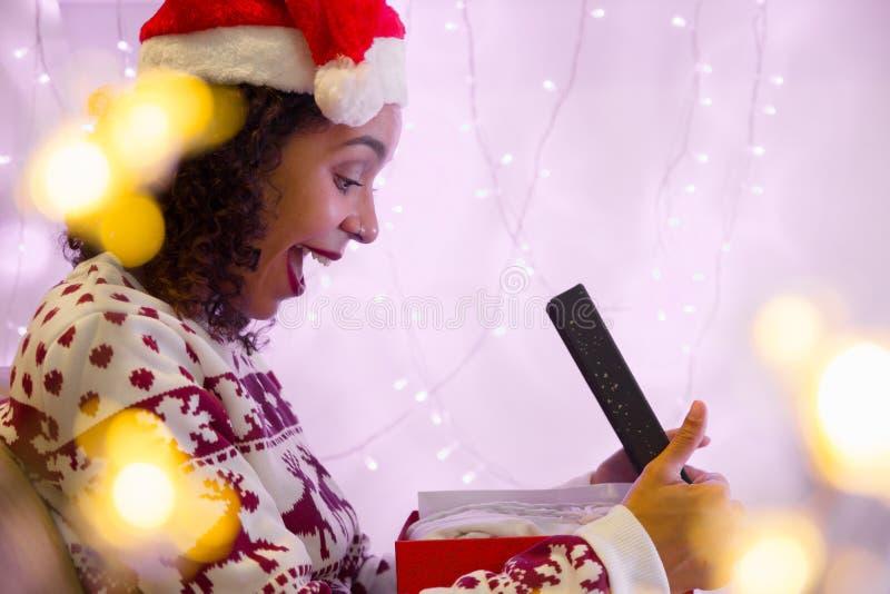 La fille stupéfaite avec le chapeau de Noël et le chandail saisonnier ouvre le cadeau photographie stock libre de droits
