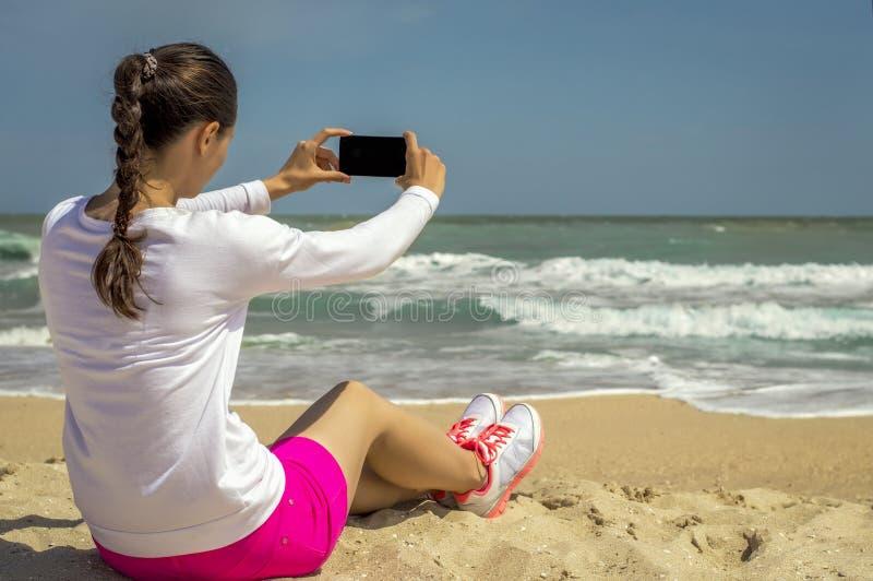La fille sur la plage fait le selfie photographie stock