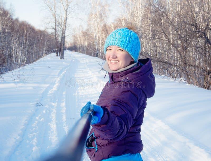 La fille sur le fond d'une forêt d'hiver fait le Se de photo images stock