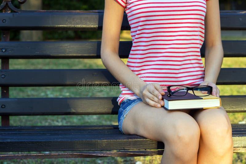 La fille sur un banc en parc avec un livre et des verres noirs dans elle recouvrement Un étudiant en parc lisant un livre photographie stock