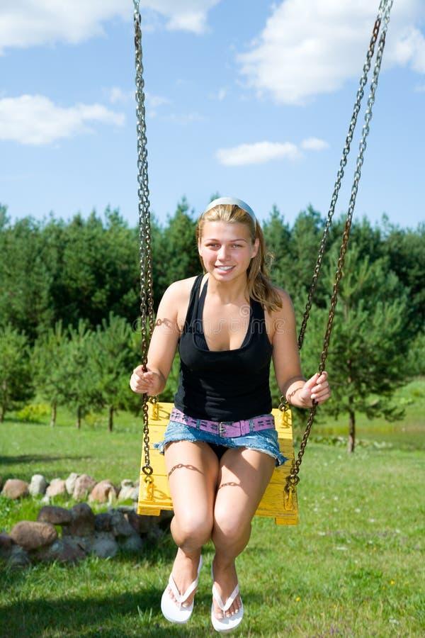 La fille sur une balançoir image libre de droits