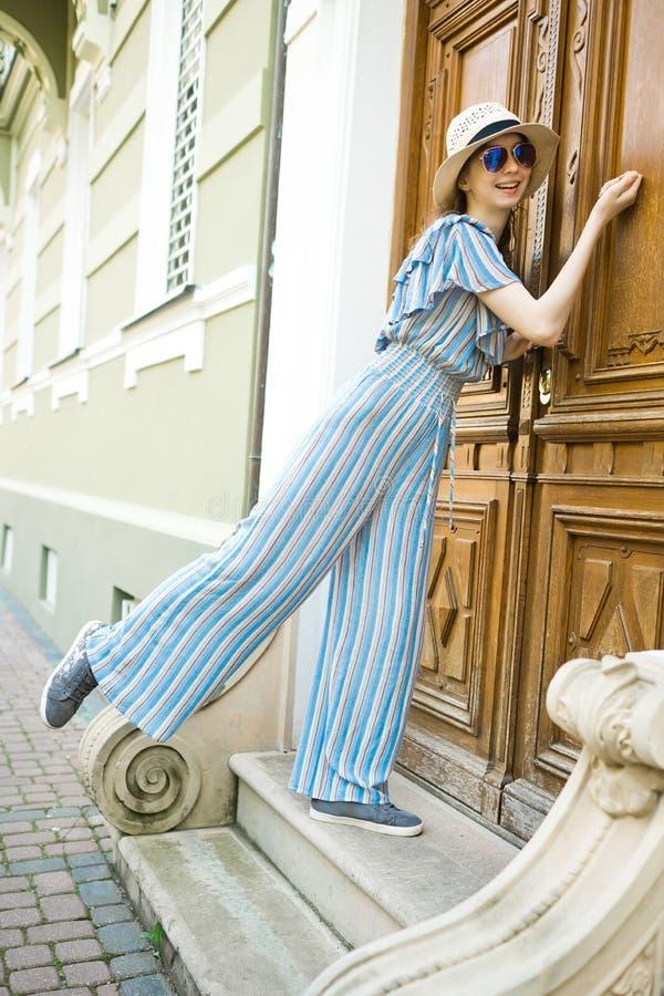 La fille Teenaged dans la robe de salopette frappe sur la porte de cru image stock