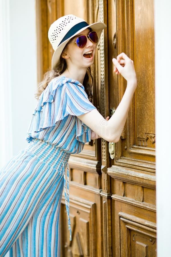 La fille Teenaged dans la robe de salopette frappe sur la porte de cru photographie stock