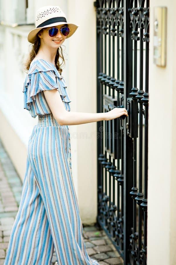 La fille Teenaged dans la robe de salopette ouvre les portes forgées illustration libre de droits
