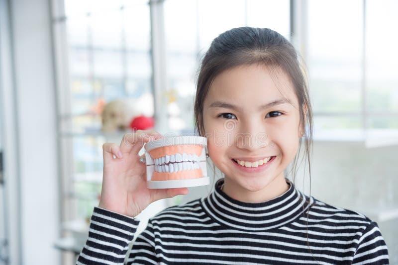 La fille tenant des dents modèlent et des sourires images stock