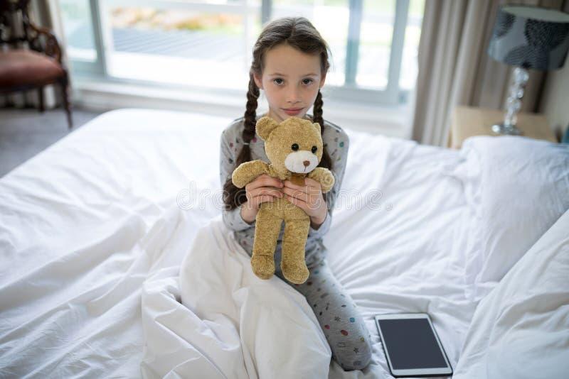 La fille tenant le nounours concernent le lit dans la chambre à coucher images stock