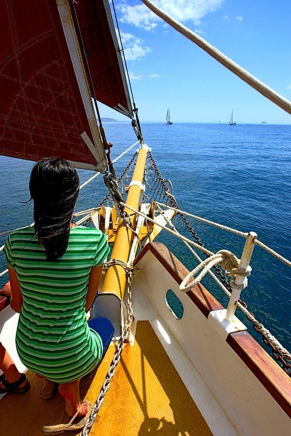 La fille tendre sur le yacht avec les voiles rouges pense à l'avenir image stock