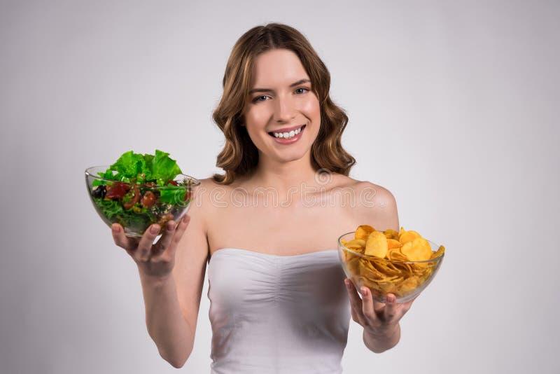 La fille tient la cuvette de salade et de pommes chips d'isolement photos libres de droits