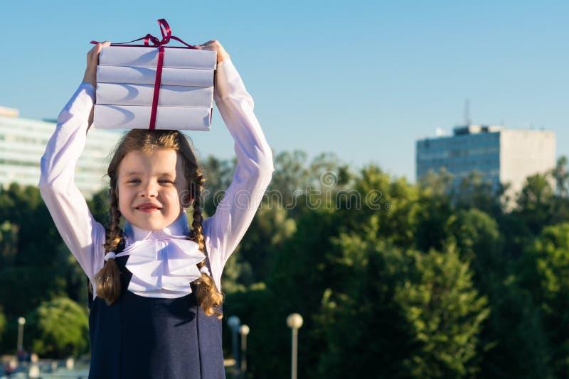 La fille tient des manuels pour l'école sur la tête devant le fond d'école image libre de droits