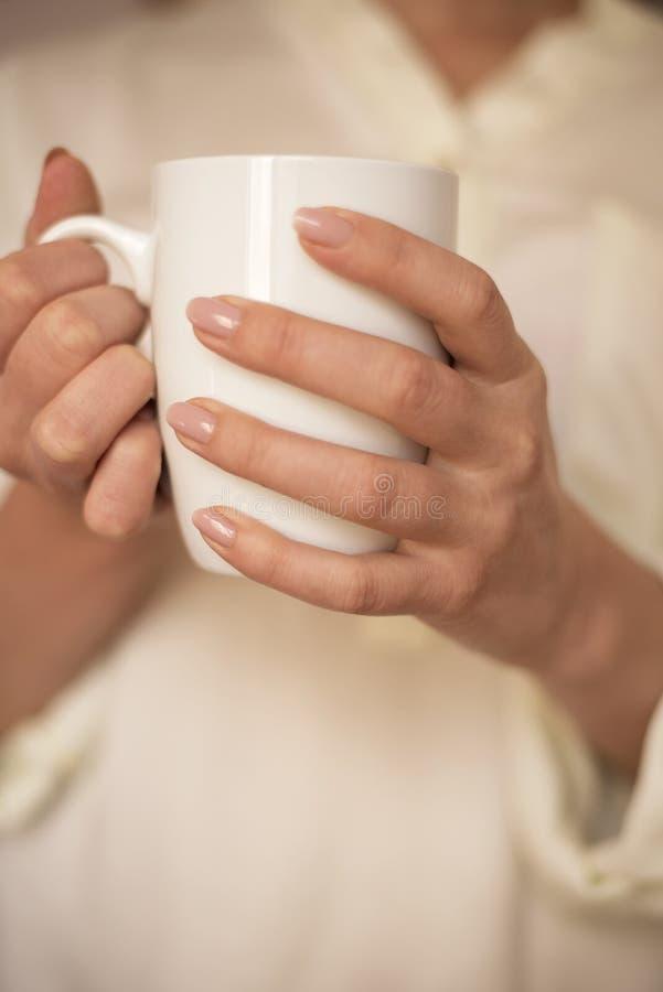 La fille tient la tasse blanche dans des mains Tasse blanche pour la femme, cadeau Mains femelles tenant la tasse chaude de café  image stock