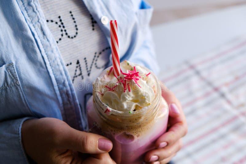 La fille tient la tasse de café rose avec de la crème, la guimauve et la décoration Lait de poule, cocktail Café de licorne, nour photo libre de droits