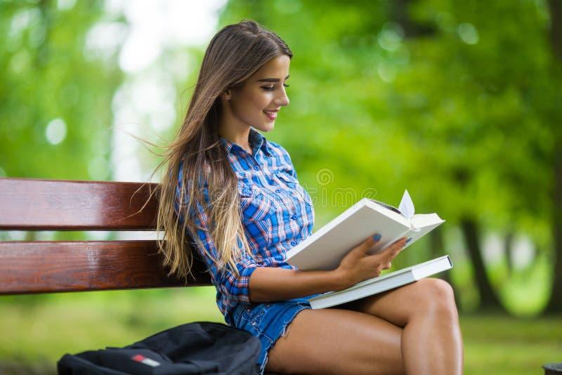 la fille tient le livre se reposent en parc images libres de droits