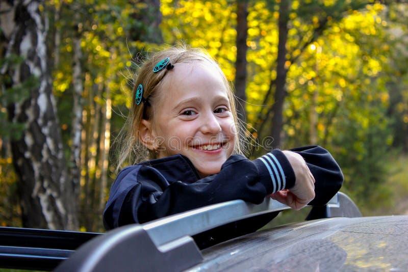 La fille tient le rail de la voiture et sourit images libres de droits