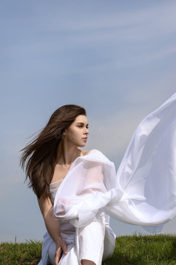 La fille tient le tissu dans des mains ondulant dans le vent photos stock