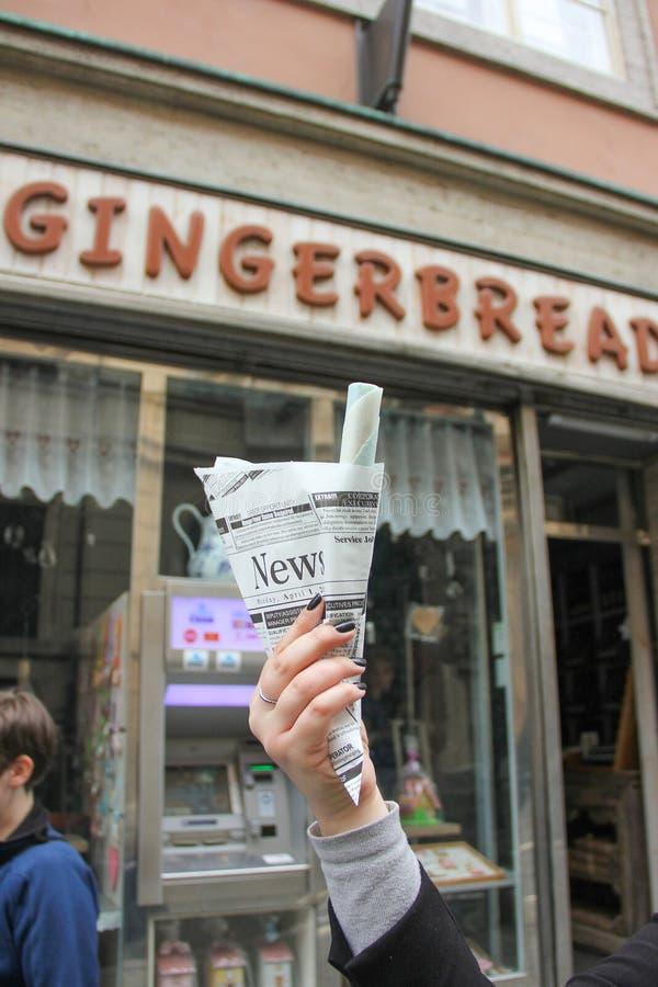 La fille tient les gaufrettes douces de souvenir roulent en journal sur le fond du magasin de café de gingerbreas photographie stock