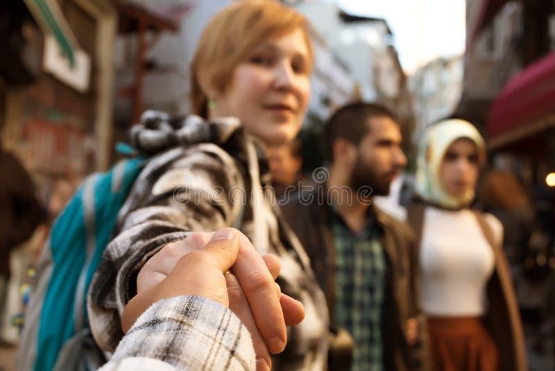 La fille tient quelqu'un main et marche sur la rue serrée de ville photos libres de droits