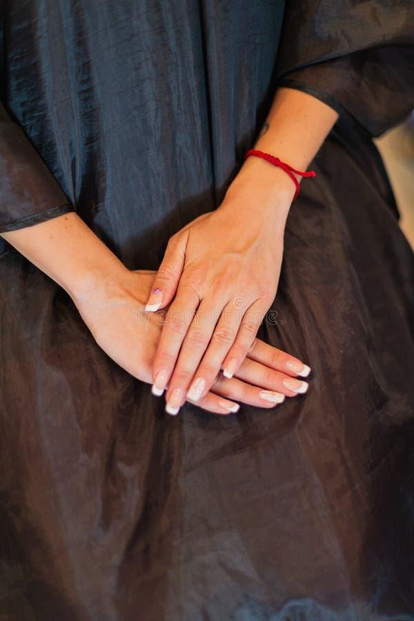 La fille tient ses mains sur ses genoux photo stock