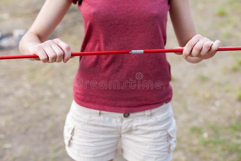 La fille tient un arc de la tente Fermez-vous vers le haut du détail de la tente de camping Poteaux en aluminium de tente Process images stock