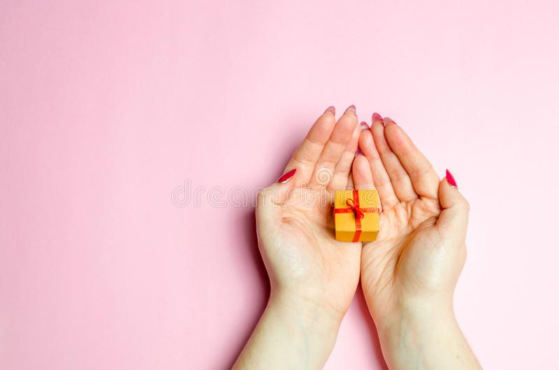 La fille tient un cadeau dans les paumes, mains Présents de concept pour vos aimés la Saint-Valentin photo libre de droits