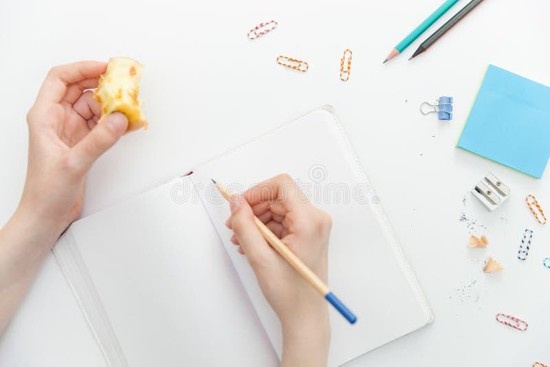 La fille tient un crayon et une pomme mordue dans des ses mains et dispose à écrire dans un carnet images libres de droits