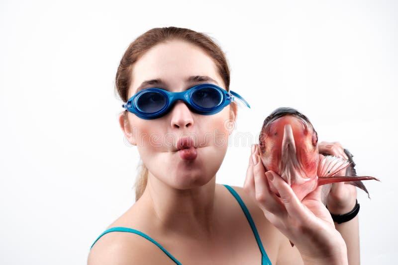 La fille tient un poisson dans des ses mains avec un visage drôle photo stock