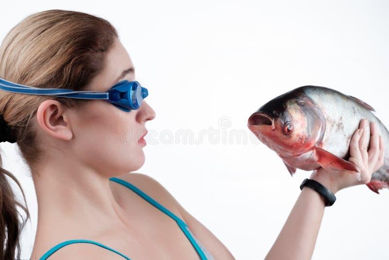 La fille tient un poisson dans sa main photographie stock libre de droits