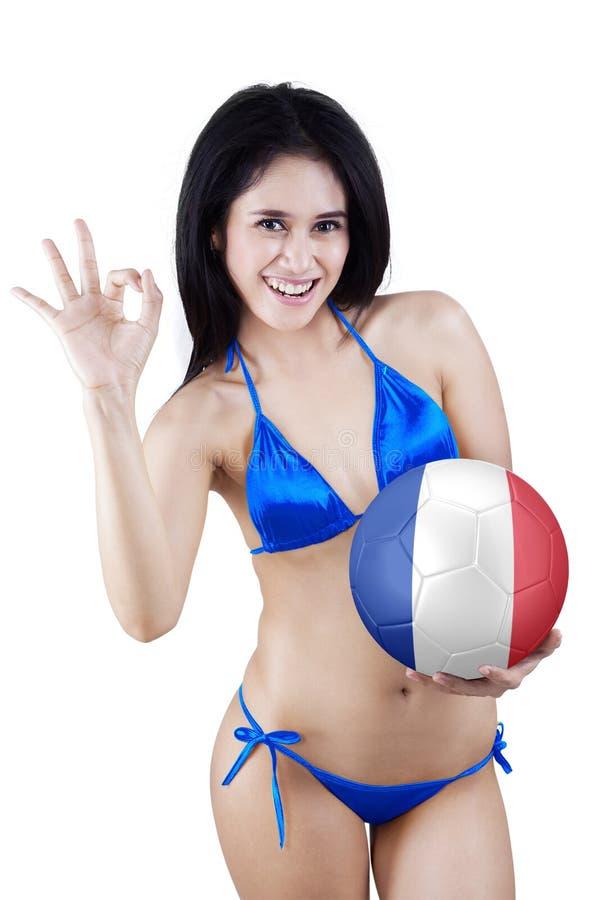 La fille tient une boule et montre le signe parfait image stock