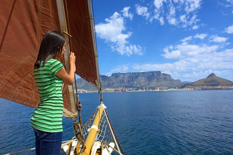 La fille timide sur le yacht avec les voiles rouges regarde des ondes photographie stock