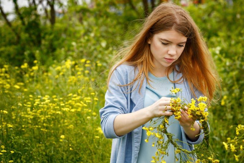 La fille tisse une guirlande des wildflowers image stock