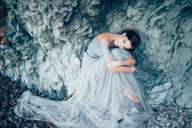 La fille très belle de brune dans une longue robe grise de dentelle et de Tulle, le voile s'assied avec sa tête cintrée et étreig image stock