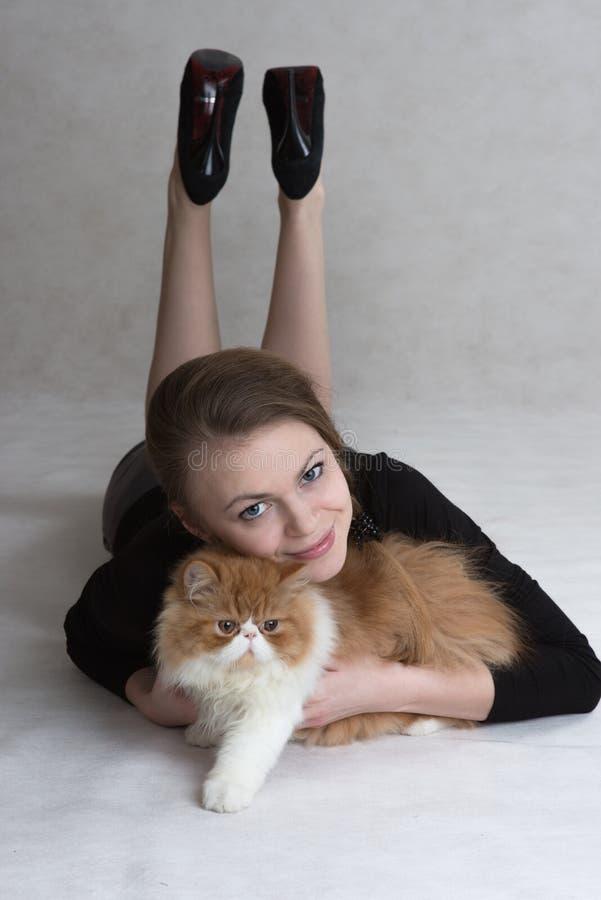 La fille très gentille tient un chaton rouge image stock