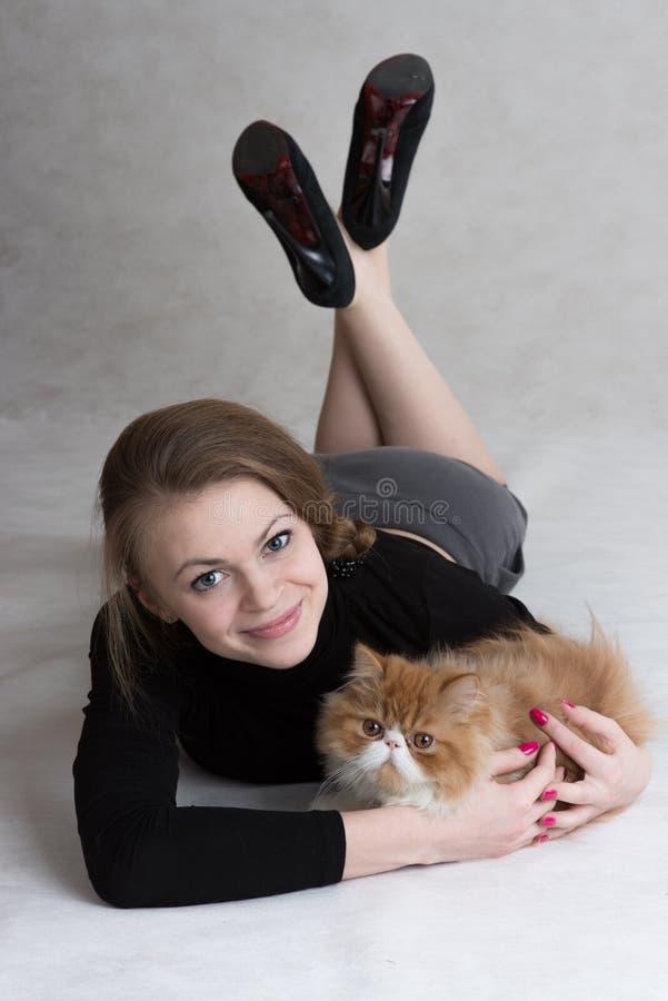 La fille très gentille tient un chaton rouge photo libre de droits