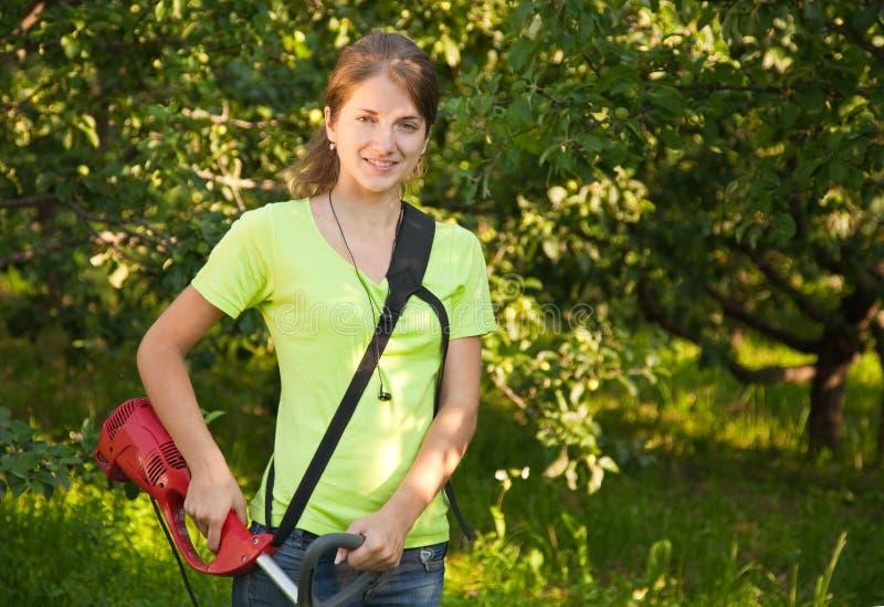 La fille travaille avec le herbe-coupeur photos stock