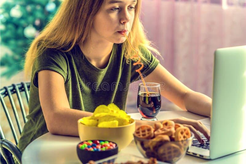 La fille travaille ? un ordinateur et mange des aliments de pr?paration rapide photo stock