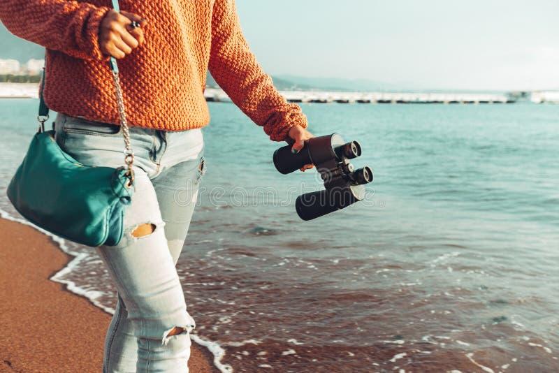 La fille trimardante méconnaissable marche le long du bord de la mer, avec des jumelles Scout Wanderlust Holidays Concept images libres de droits
