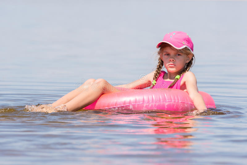 La fille triste dans un chapeau flottant en rivière s'est assise sur le cercle de natation photos libres de droits