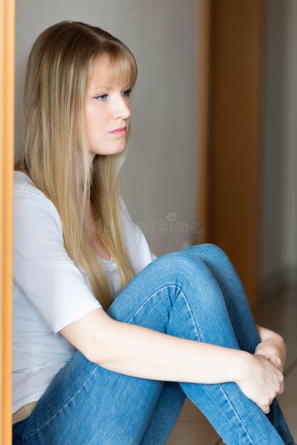 La fille triste s'assied sur l'étage photos libres de droits