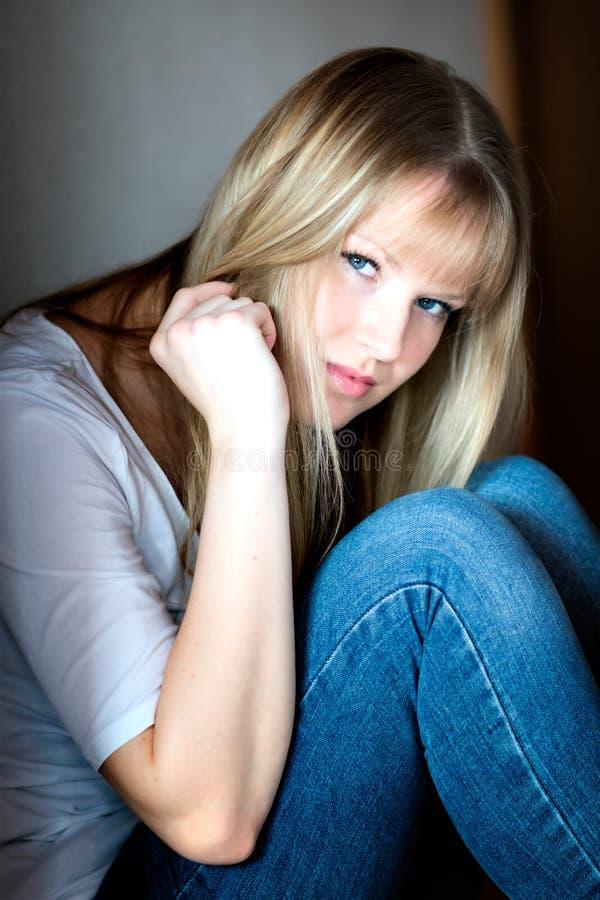 La fille triste s'assied sur l'étage photographie stock