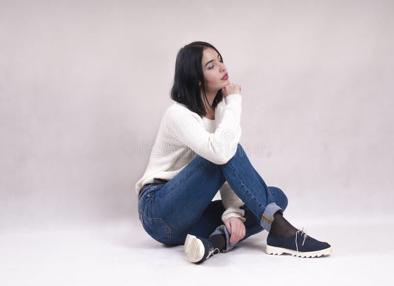 La fille triste s'assied sur le plancher dans la solitude de solitude de dépression de jeans photo stock