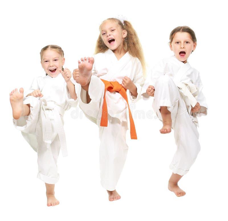 La fille trois gaie s'est habillée dans une jambe blanche de coup-de-pied de kimono images libres de droits
