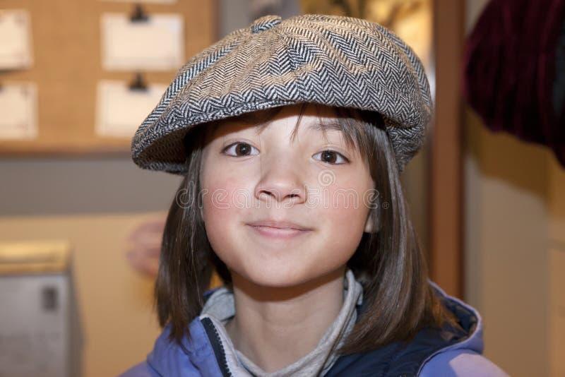 La fille utilise le vieux chapeau. image libre de droits