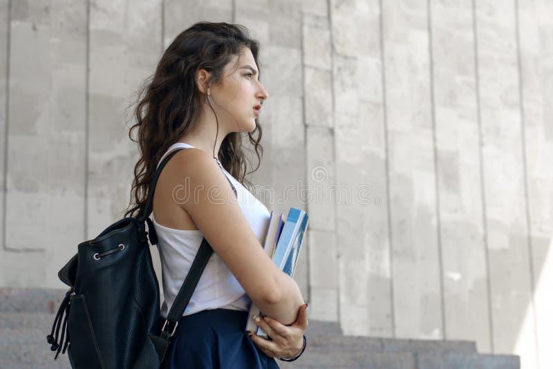 La fille va avec des livres dans des ses mains photo stock