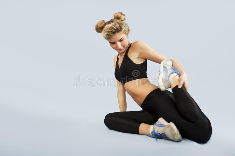 La fille va chercher dedans des sports sur un fond d'isolement faisant différents exercices de la gymnastique et de la forme phys photo libre de droits