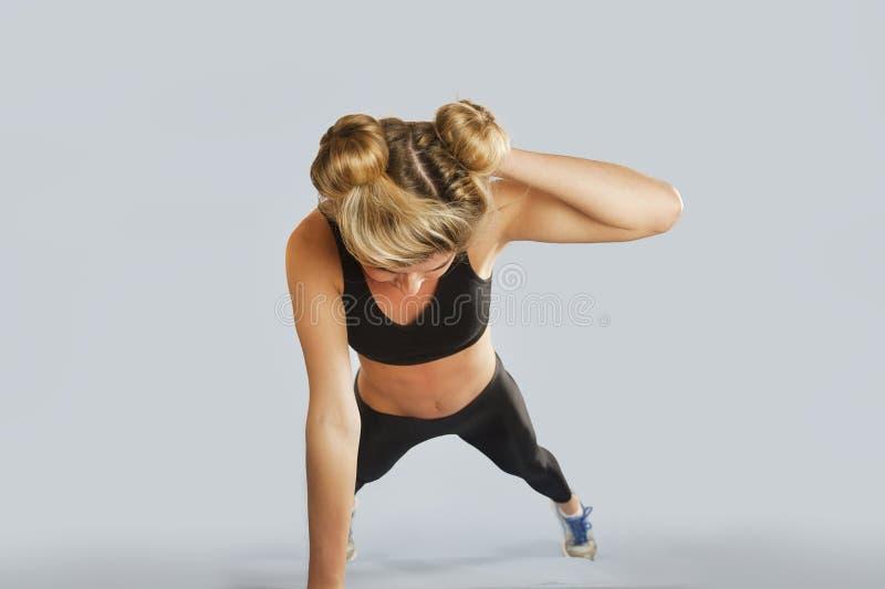 La fille va chercher dedans des sports sur un fond d'isolement faisant différents exercices de la gymnastique et de la forme phys photographie stock