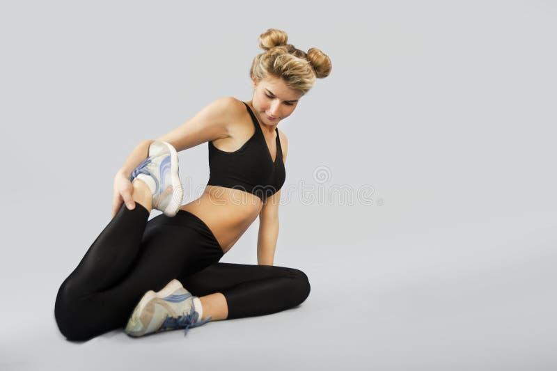 La fille va chercher dedans des sports sur un fond d'isolement faisant différents exercices de la gymnastique et de la forme phys photo stock