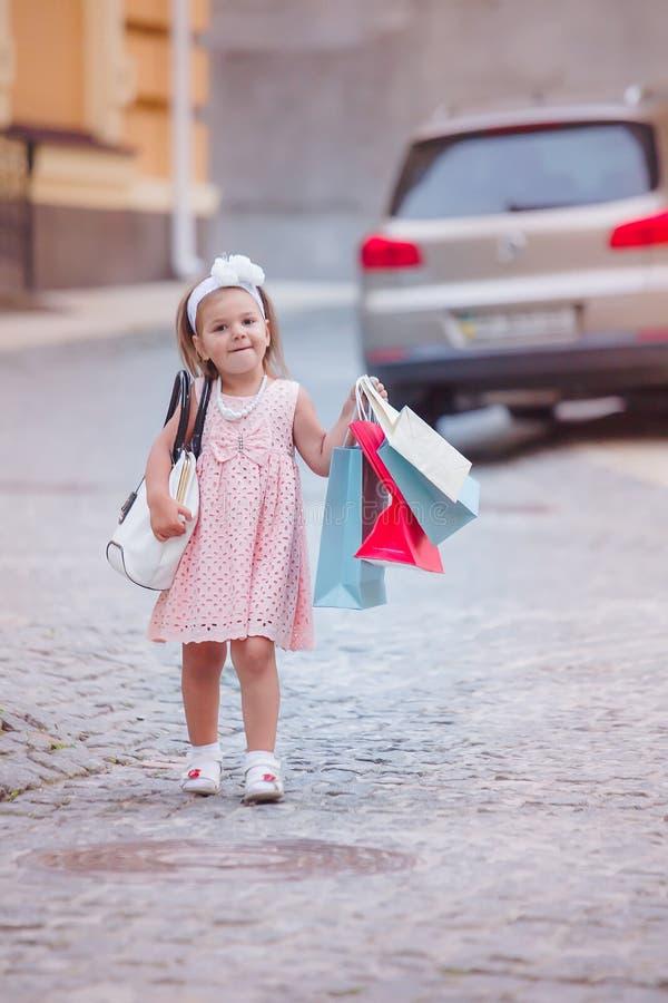 La fille va faire des emplettes avec les paquets ou les paniers marqués dans la ville Achat avec l'enfant tout en marchant le lon image stock