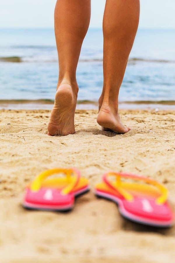 La fille va nager en mer Pieds sur le sable photographie stock libre de droits