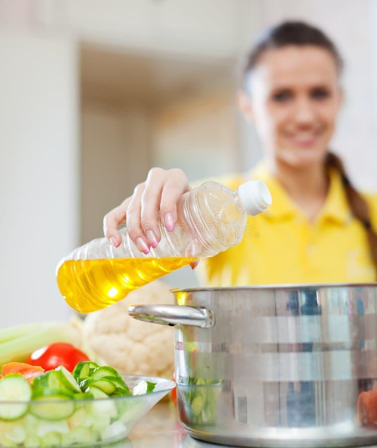 La fille verse l'huile de la bouteille dans la casserole image stock