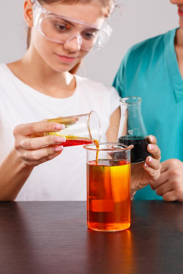 La fille verse le liquide orange d'un petit verre de mesure dans un grand verre photographie stock libre de droits
